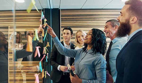 Marketingspezialisten ordnen Haftnotizen auf einer Glaswand an.