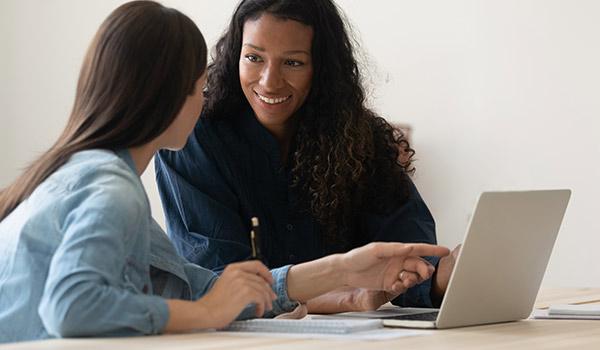 Zwei Frauen sitzen an einem Computer und besprechen einen Entwurf für eine E-Mail.