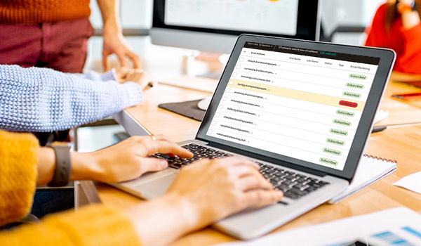 Ein Marketingspezialist betrachtet auf einem Laptop eine Verteilerliste, in der ein nicht erreichbarer Kontakt rot gekennzeichnet ist.