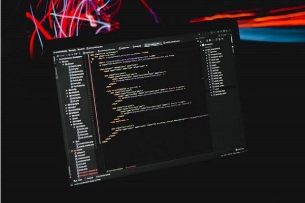 Ein Computer, über dem farbige digitale Ströme schweben.