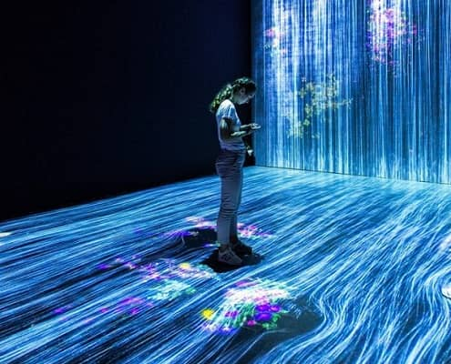 Eine junge Frau steht in einem Flusslauf aus digitalen Strömungslinien.
