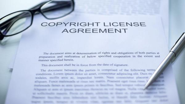 Neben einem Dokument zur Vereinbarung der Urheberrechte liegen ein Stift und eine Brille.