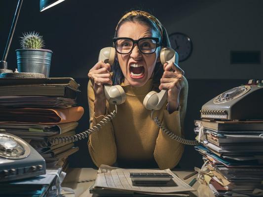 Eine überforderte Person mit zwei Telefonhörern in der Hand sitzt an einem Schreibtisch voller Akten.