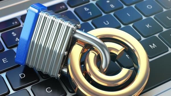 Ein Copyright-Symbol auf einer Computertastatur, das mit einem Vorhängeschloss gesichert ist.