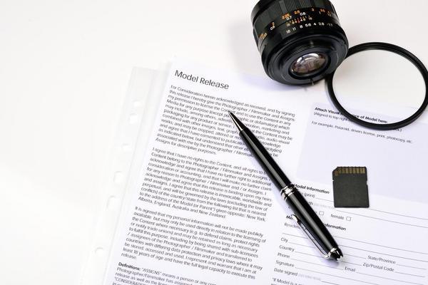 Neben einem Kameraobjektiv liegen eine Speicherkarte, ein Stift und eine Einverständniserklärung mit der Überschrift Model Release.