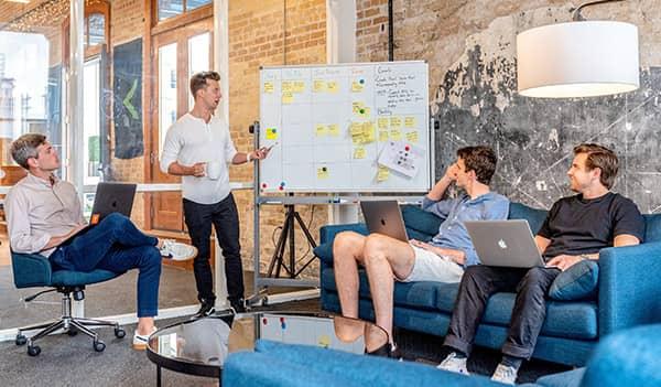 Eine Besprechung unter jungen Kollegen zur strategischen Planung für das E-Mail-Capturing in einem modernen Büro.