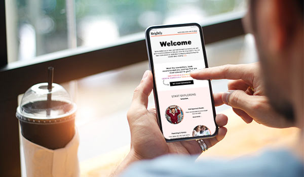 Ein Mann trinkt Kaffee und liest eine Willkommens-E-Mail auf einem Smartphone, eines der kleinen notwendigen Elemente, wenn man einen E-Mail-Verteiler erstellen möchte.