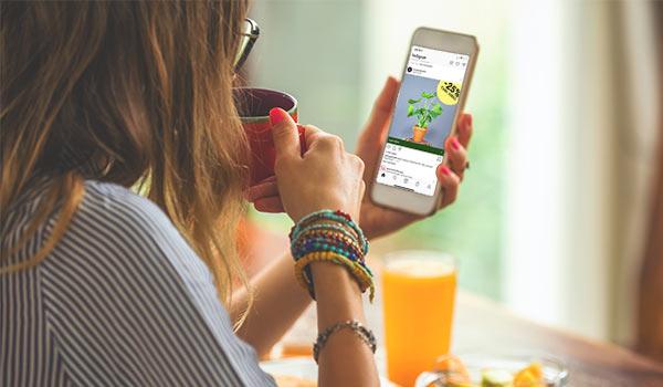 Eine Frau trinkt Kaffee und schaut sich auf ihrem Handy eine Anzeige für Zimmerpflanzen auf Instagram an.