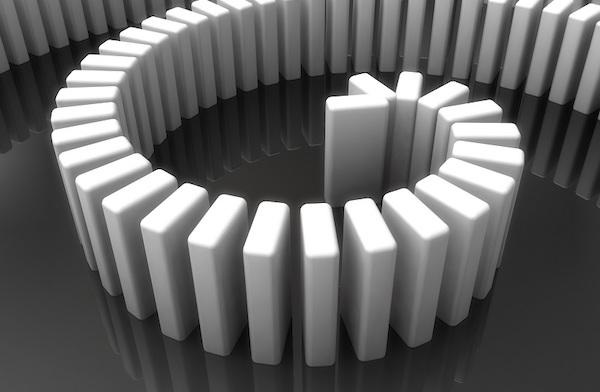 Eine Reihe von nebeneinander aufgestellten Dominosteinen.