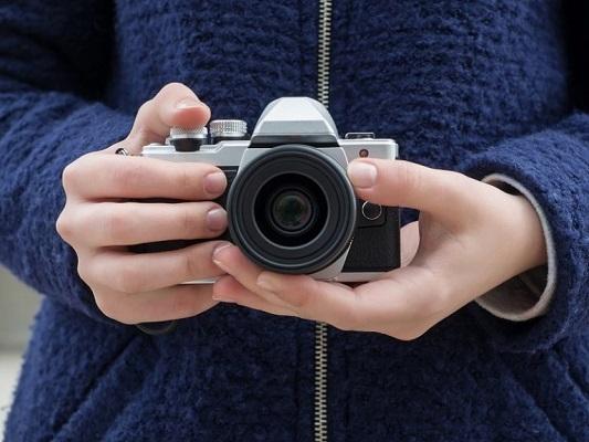 Eine Frau hält eine klassische Olympus-Kamera in der Hand und möchte wahrscheinlich bald ORF in AI konvertieren.