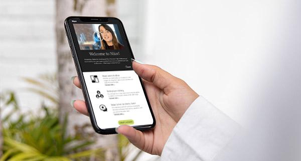 Eine Hand hält ein Smartphone, das eine E-Mail mit Video zeigt, ein anschauliches Beispiel für Video-E-Mail-Marketing.