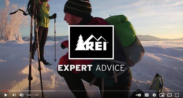Videostandbild mit dem Logo von REI über der Szene einer Schneeschuhwanderung.