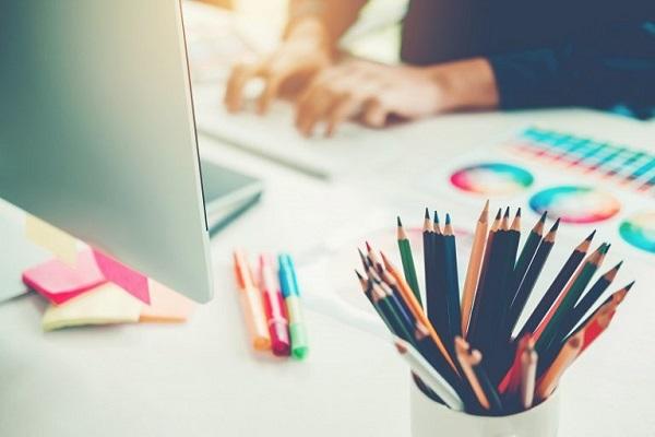 An einem Schreibtisch mit farbenfrohem Design möchte eine Person auf ihrem Laptop Adobe Illustrator benutzen.