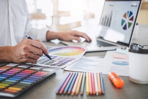 Ein Grafikdesigner wählt anhand einer Vorlage die gewünschten Farben aus.