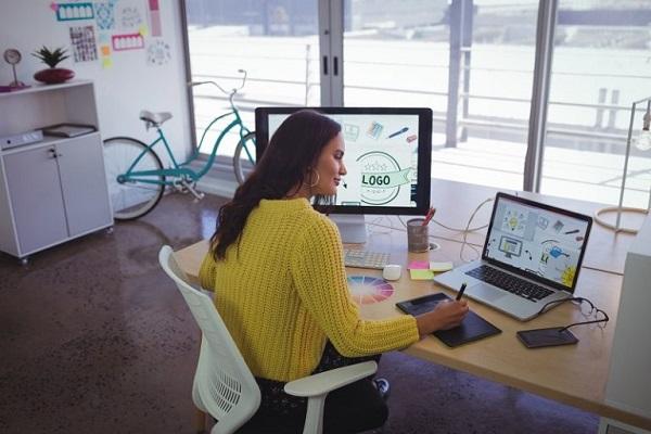 Ein Designer bearbeitet mit Laptop und Computer Bilder, die er in Adobe Illustrator benutzen kann.