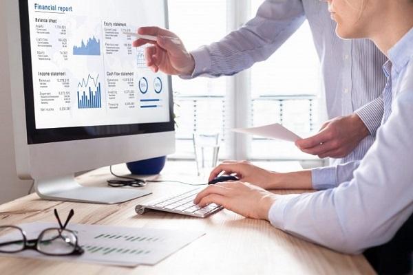 Zwei Mitarbeiter recherchieren auf einem Computer Finanzunterlagen.
