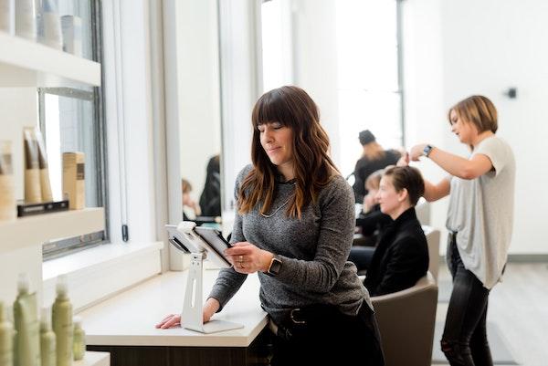 Eine Frau in einem geschäftigen Friseursalon benutzt ein iPad.