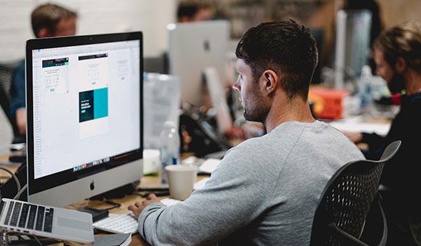 Ein Mann sitzt im Büro an einem Computer und entwirft eine E-Mail für kostenloses E-Mail-Marketing.
