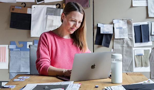 Eine Frau in einem rosafarbenen Pullover arbeitet an einem Laptop-Computer, um sie herum hängen Stoffmuster.