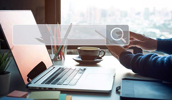 Ein Laptop, über dem ein Suchfeld schwebt, symbolisch für die Möglichkeit, nach Datenobjekten zu suchen, die mithilfe von Metadaten-Standards korrekt beschrieben wurden.
