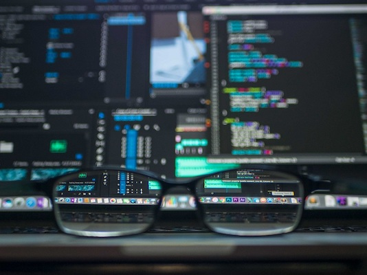 Mehrere Bildschirme voller Daten durch eine Brille betrachtet.
