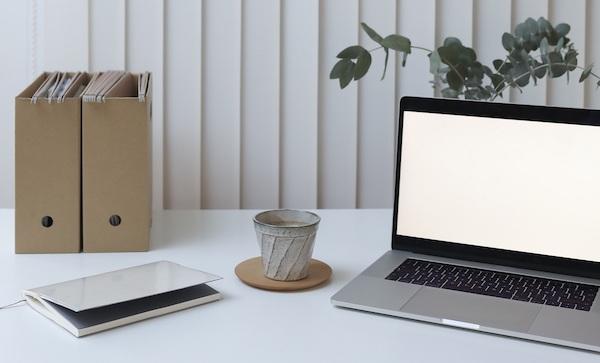Auf einem Tisch neben einem Laptop befinden sich Ordner, eine Tasse und ein Buch.