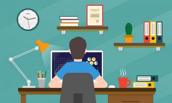 Ein Mann sitzt zu Hause an einem Schreibtisch und verwendet seinen Computer, weil er JPG in EPS konvertieren möchte.